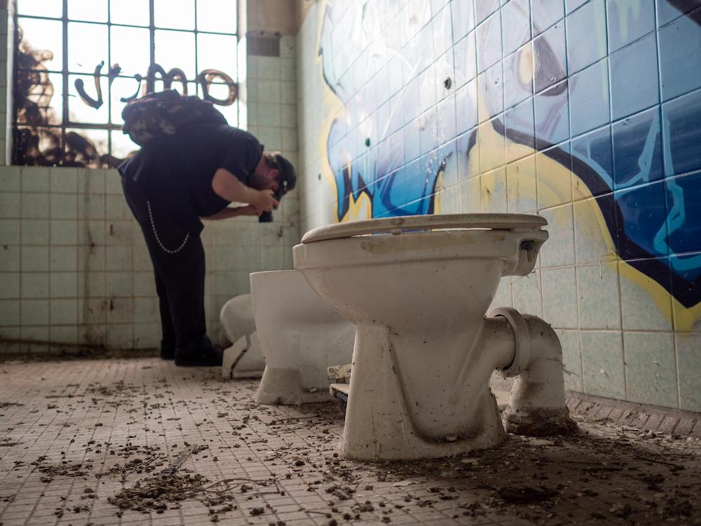 """Durchblick: Toiletten und Waschraum einer """"nachgenutzten"""" Fabrik."""