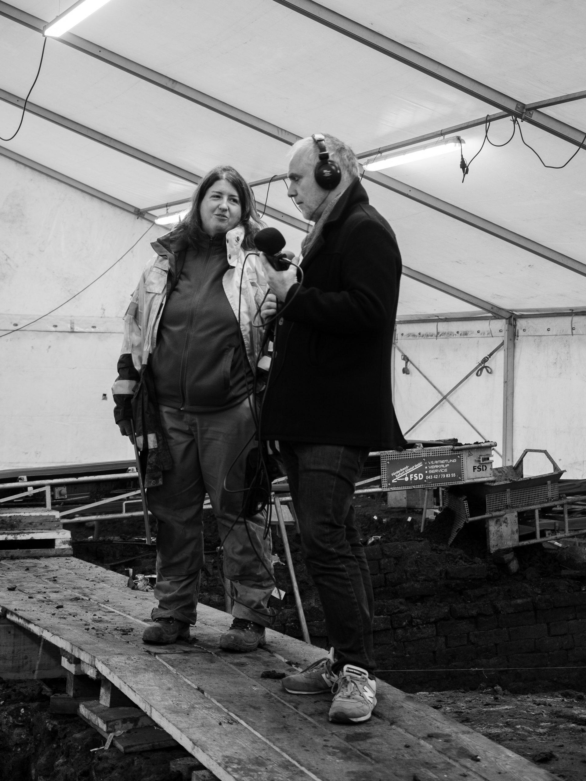 Christoph und Judith stehen auf der Ausgrabungsfläche am Hopfensack